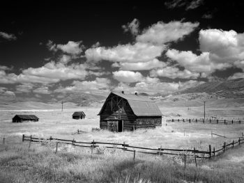 black and white photo of barn in foothills on a partly cloudy day